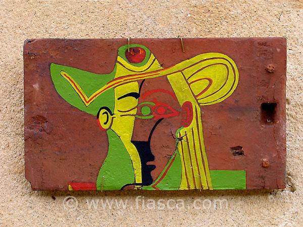 Femme assise au chapeau jaune et vert